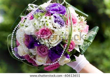 Colorful wedding bouquet in bride's hands - stock photo