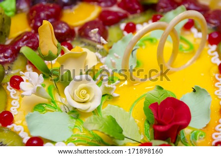 colorful wedding cake with roses and rings, closeup - stock photo