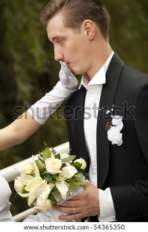 Colorful wedding shot of bride shutting groom's mouth