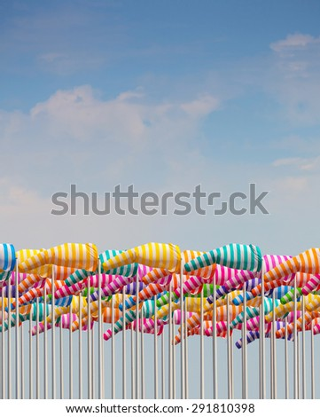 Colorful windsocks against cloudy blue sky - stock photo