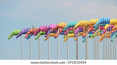 Colorful windsocks on poles against blue sky - stock photo