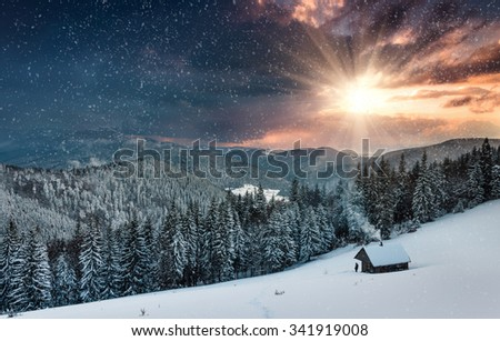 Colorful winter evening in the mountains at sunset. Dramatic overcast sky and snowing. View of the old farm and tourist near. - stock photo