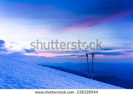 Colorful winter sunrise in mountains. Ski sticks or trekking poles. - stock photo