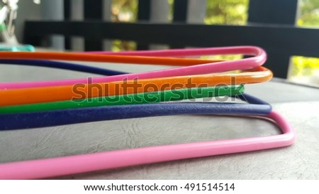 Colorful wire on gray floor with blur fence and tree background.