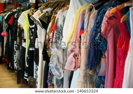 Colorful women's dresses on hangers in a retail shop - stock photo