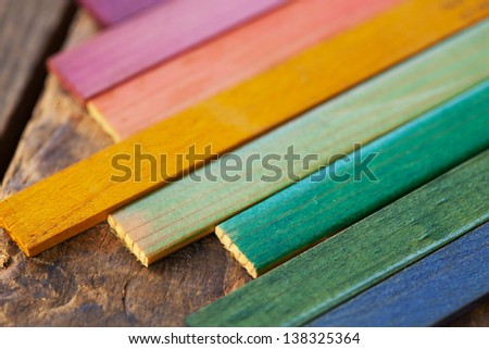 Colorful wood stain color test samples, on rough wood. Shallow depth of field. - stock photo