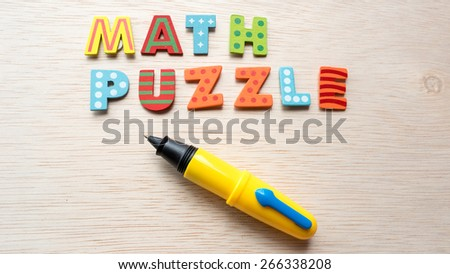 Colorful wooden alphabet letter set with cute pen and text MATH PUZZLE. Concept of fun preschool or back to school. Shot with natural light. Slightly defocused and close-up shot. Copy space.