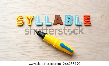 Colorful wooden alphabet letter set with cute pen and text SYLLABLE. Concept of fun preschool or back to school. Shot with natural light. Slightly defocused and close-up shot. Copy space.