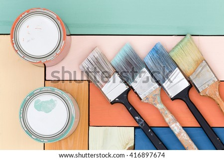 Colorful wooden background of stained boards inlaid in a pattern with two cans of stain and four neatly arranged paintbrushes on top - stock photo