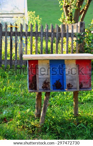 Colorful wooden beehive, antique style on a green meadow. - stock photo