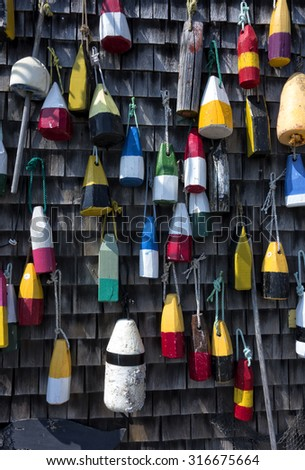Colorful wooden buoys against a shingled wall.