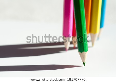 Colorful wooden crayons edgewise on white background, macro with shallow dof. Selective focus. - stock photo