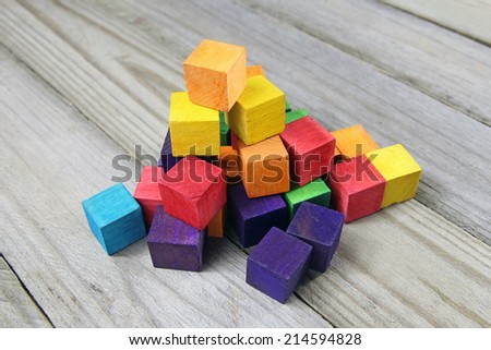 colorful wooden cubes on wood background - stock photo