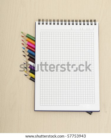 colorful wooden pencils and nootebook on table