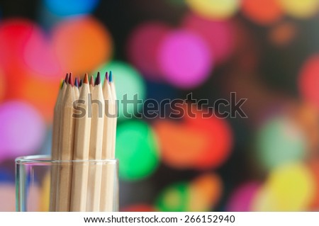 Colorful wooden pencils  in  jar standing on colorful  background