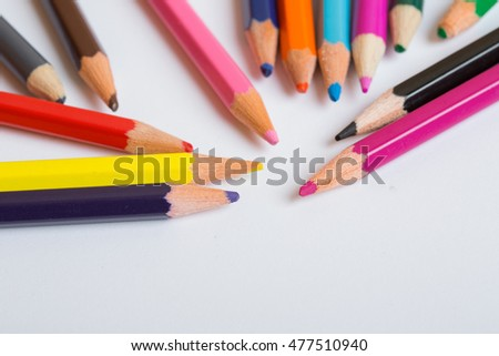 Colorful wooden pencils on a white paper