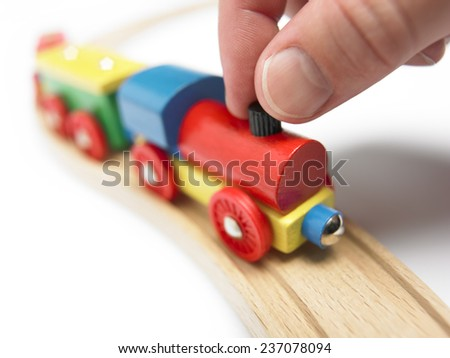 Colorful wooden toy train with hand isolated on white. Horizontal - stock photo