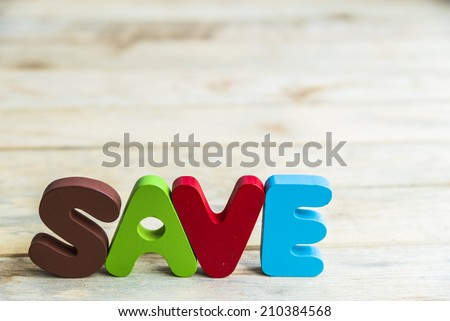Colorful wooden word Save on wooden floor - stock photo