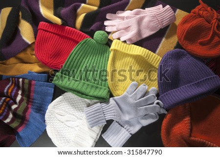 Colorful woolen scarf, hats and gloves background - stock photo