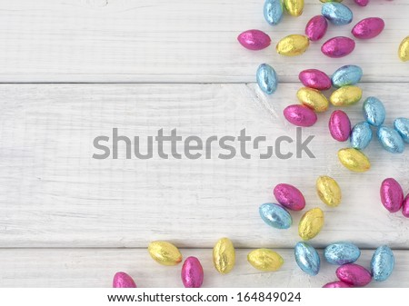 Colorful Wrapped Chocolate Easter Eggs Scattered on White Board Background with room or space for text, copy or words.  Horizontal - stock photo