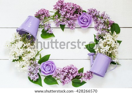 Colorful wreath of lilac with decorative watering can, bucket and candles . Use for floral backgrounds, holiday greetings and invitations postcards. Top view, space for text - stock photo