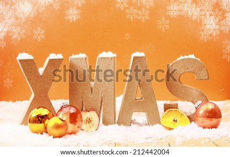 Colorful Xmas background with falling snowflakes and wooden letters spelling Xmas covered in snow with orange and gold decorations and fruit on a warm toned orange background - stock photo