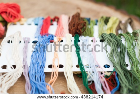 Colorful yarn for crafts, colored threads for embroidery on a wooden table - stock photo