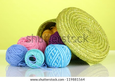 Colorful yarn for knitting in green basket on green background - stock photo
