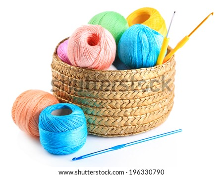 Colorful yarn for knitting with napkin in wicker basket and crochet hook, isolated on white - stock photo