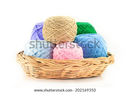 Colorful yarn in wicker basket isolated on white - stock photo