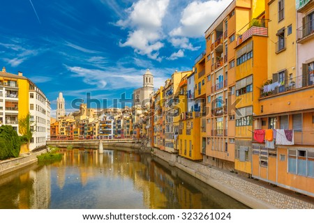 Colorful yellow and orange houses and bridge Pont de Sant Agusti reflected in water river Onyar, in Girona, Catalonia, Spain. Church of Sant Feliu and Saint Mary Cathedral at background. - stock photo