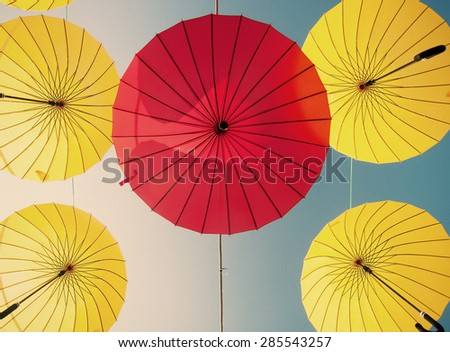 colorful yellow and red umbrellas under the beautiful cloudy sky