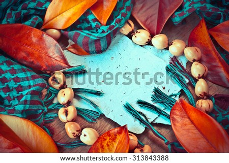 Colorful yellow orange leaves of magnolia on wooden table. Fall theme, Autumn concept background with copy space, blue checkered scarf and copy space as white paper and large wooden beaded necklace - stock photo