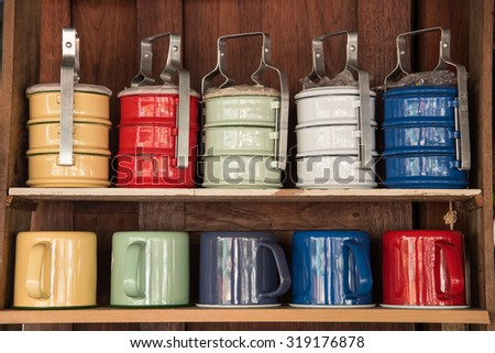 Colorful zinc cup and tiffin on wooden shelves - stock photo