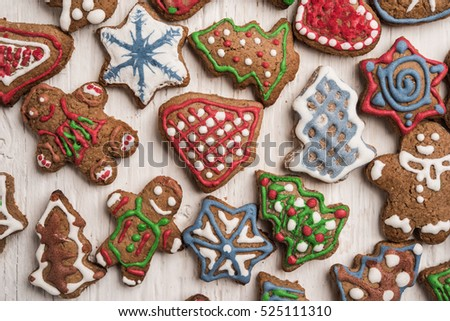 Colorfully Christmas cookies on rustic wooden background, gingerman and tree