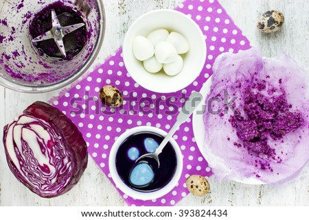 Coloring Easter Eggs from natural red cabbage in blue color. Food concept for Easter holidays. Cooking process and ingredients on white background top view - stock photo