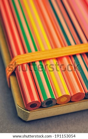 Coloring pencils fixed to a notebook with a rubber band