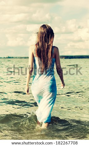 Colorized vintage outdoor portrait of Young beautiful slavonic girl posing on the beach