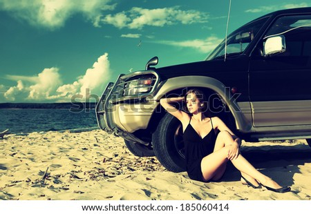 Colorized vintage outdoor portrait of Young beautiful slavonic girl sitting on the sand in black dress near the off-roader's wheel  - stock photo