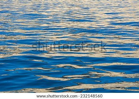 Colors from an island and early morning sunrise cause rich, blue and tan reflections on the surface of the water.  - stock photo