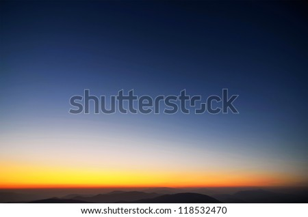 Colors of evening sky above the mountains and ridges - stock photo