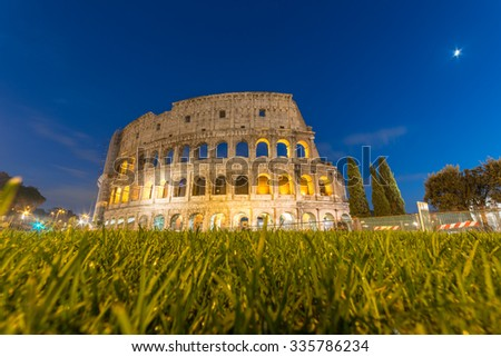 Colosseum Rome, Beautiful Panorama View Illuminated Colosseum with Out of Focus Grass foreground at Night viewed from the grassy area from Piazza del Colosseo near the main entrance, Rome, Italy - stock photo