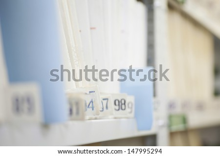 Colour coded filing system on library shelves - stock photo