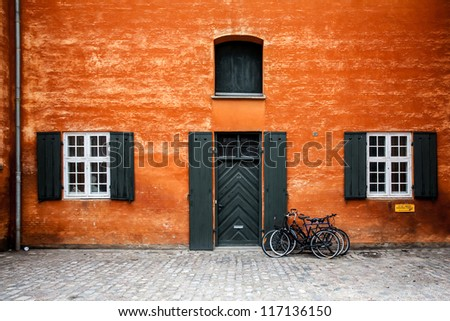 colour houses in copenhagen denmark with a bike against a wall - stock photo