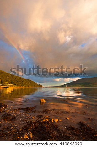 Colour image of Carlingford Lough in Northern Ireland. Green hills and the Irish Sea. Take on a summer's evening. Sail boats moored in the distance. Dramatic cloudy sky with rainbow forming. - stock photo