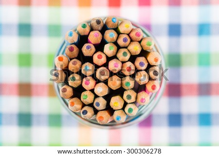 Colour pencils in the glass over colorful background - stock photo