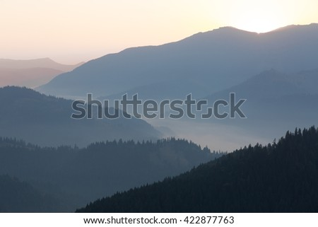 Colour picture of mountains and a valley in a foggy morning at sunrise