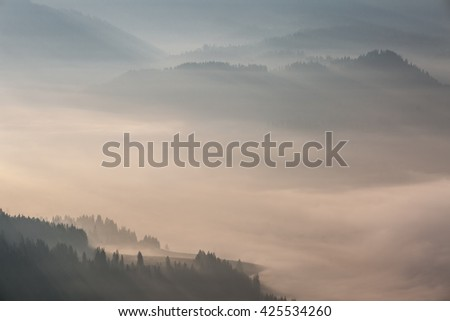 Colour picture of mountains and a valley in a foggy morning at sunrise - stock photo