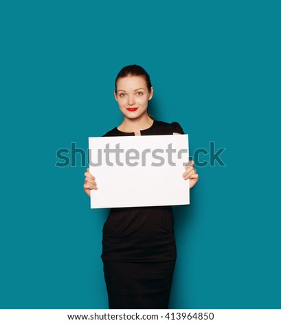 Colour studio portrait of pretty smiling girl showing empty blank board. Blue background isolated - stock photo