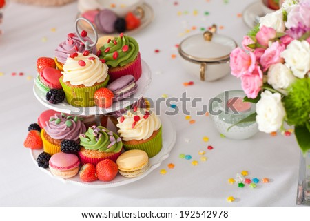 Coloured beautiful arrangement of cupcakes, fruits and flowers on a table - stock photo